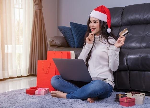 Femme en bonnet de noel, pensant acheter en ligne pour un cadeau de noël avec ordinateur portable dans le salon