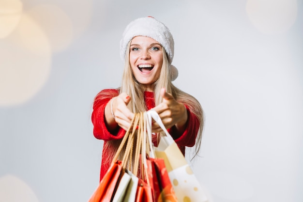 Femme en bonnet de noel avec des sacs à provisions dans les mains