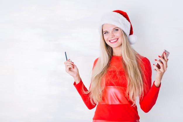 Femme en bonnet de noel avec smartphone