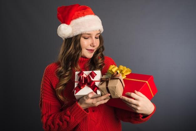 Femme avec bonnet de noel tenant des cadeaux de noël