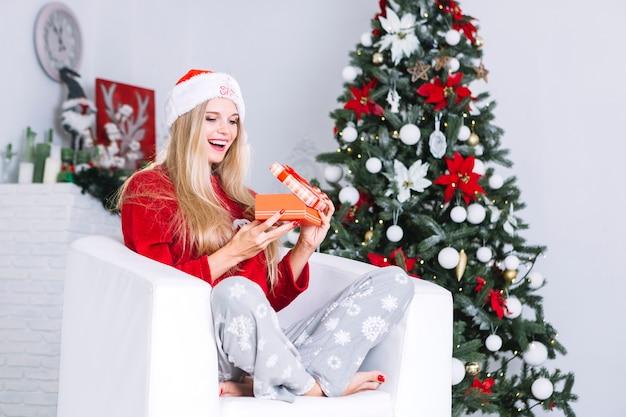Femme en bonnet ouvrant petite boite cadeau