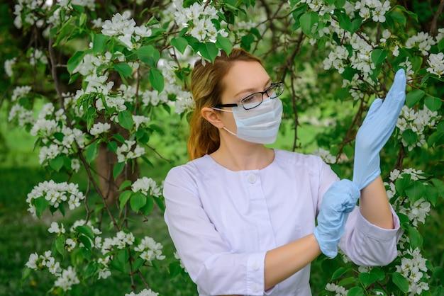 Femme botaniste en blouse blanche, masque médical et lunettes met des gants, travaille avec des plantes dans le jardin botanique