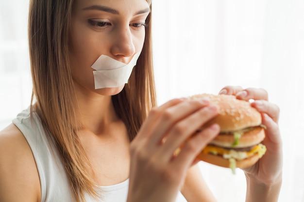Femme avec une bouche coincée essaie de manger de la mauvaise nourriture