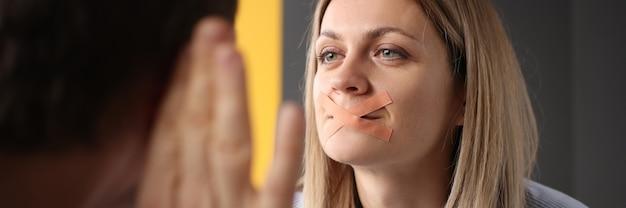 La femme avec la bouche scellée essaie de dire quelque chose à l'homme