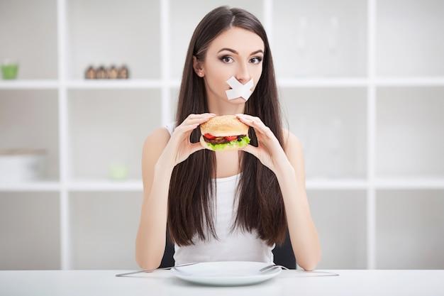 Une femme avec une bouche scellée essaie de manger un hamburger