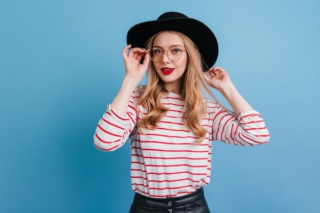 Femme bouclée au chapeau élégant regardant la caméra. photo de studio d'une fille blonde fascinante en chemise rayée.