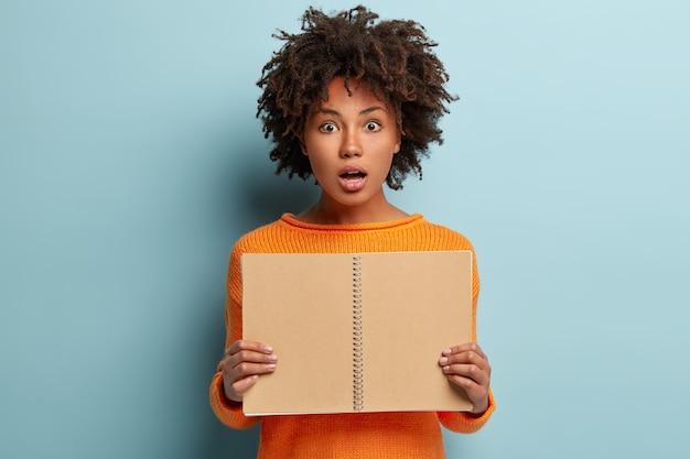 Femme bouclée aux cheveux afro, tient le bloc-notes en spirale ouvert devant, voit l'avis, choquée d'oublier une tâche ou une réunion importante, porte un pull orange, isolé sur un mur bleu. fille avec journal