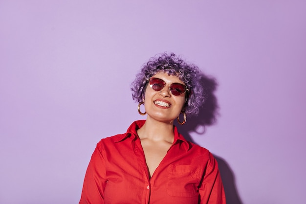 Femme bouclée aux cheveux courts avec des lunettes lumineuses élégantes, en chemise rouge à manches longues et sourit sur lilas isolé.