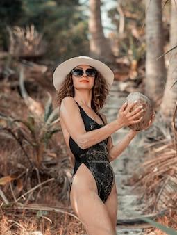 Femme bouclée en bikini noir dans la jungle avec fond de palmiers