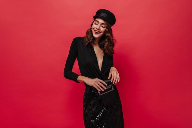 Une femme bouclée excitée en jupe noire brillante et un bonnet sourit, tient une pochette et pose sur un mur rouge isolé