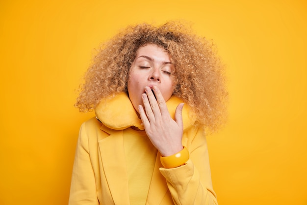 Une femme bouclée et fatiguée se sent très fatiguée a une expression endormie bâille et couvre la bouche ferme les yeux