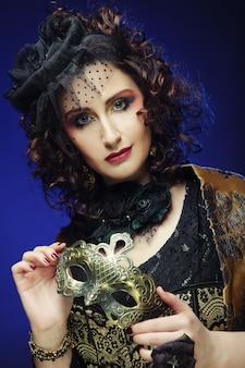 Femme bouclée avec masque. visage de carnaval.