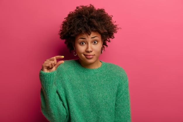 La femme bouclée mesure quelque chose de minuscule, dit qu'elle a de petits problèmes, façonne un petit objet, porte un pull vert, n'a pas l'air impressionné, pose sur un mur rose. concept de langage corporel et de taille