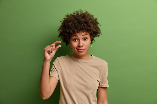 Femme bouclée non impressionnée montre un peu plus ou un petit peu de geste, démontre quelques pouces ou sentimètre, petite quantité ou signe à petite échelle, adressée dans des vêtements décontractés, isolé sur un mur vert