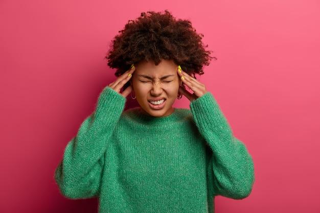 Une femme bouclée à la peau sombre et bouleversée touche les tempes, fronce les sourcils et souffre de migraine