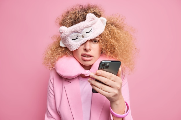 Une femme bouclée perplexe vérifie le contenu du message après s'être réveillée avec une expression mécontente à l'écran du smartphone a oublié une réunion importante porte un masque de sommeil et un oreiller à l'intérieur
