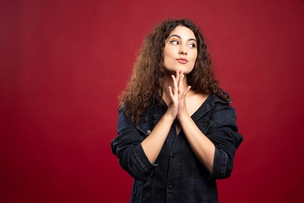 Femme bouclée regardant son côté avec ses mains fermées.