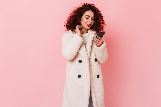 Femme bouclée avec rouge à lèvres vif habillé en manteau de fourrure écologique se penche sur son smartphone sur l'espace rose.