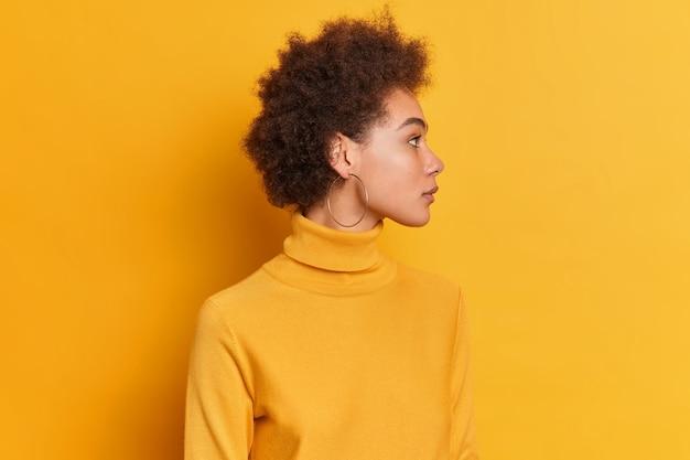 Femme bouclée se tient sur le côté, a une expression sérieuse cheveux bouclés foncés vêtus de col roulé porte des boucles d'oreilles rondes