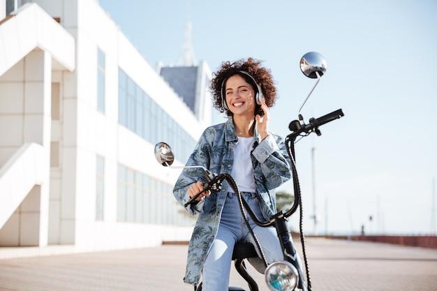 Femme bouclée souriante assise sur une moto moderne à l'extérieur et écouter de la musique