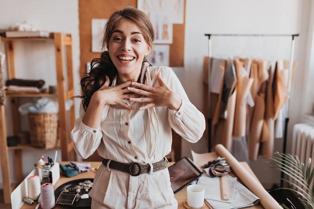Femme bouclée en tenue beige regarde joyeusement à l'avant