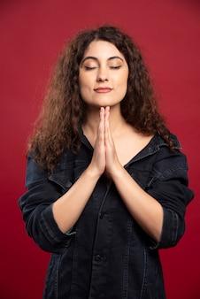Femme bouclée en veste en jean faisant de la méditation.