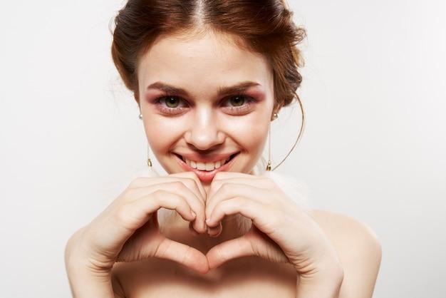 Femme avec boucles d'oreilles duveteuses maquillage lumineux émotions libre