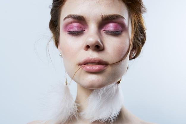 Femme avec des boucles d'oreilles moelleuses maquillage lumineux épaules nues agrandi