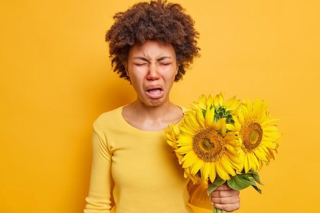 Une femme boude et fronce les sourcils a une grimace malheureuse tient un bouquet de tournesols qui provoque une réaction allergique porte un pull décontracté isolé sur un jaune vif