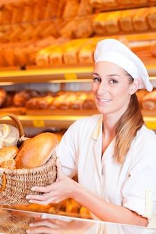Femme boulangère vendant du pain dans sa boulangerie