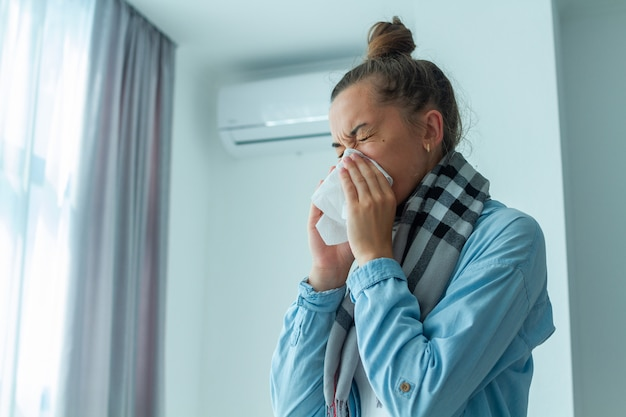 Femme bouleversée attrapé un rhume du climatiseur et éternuements