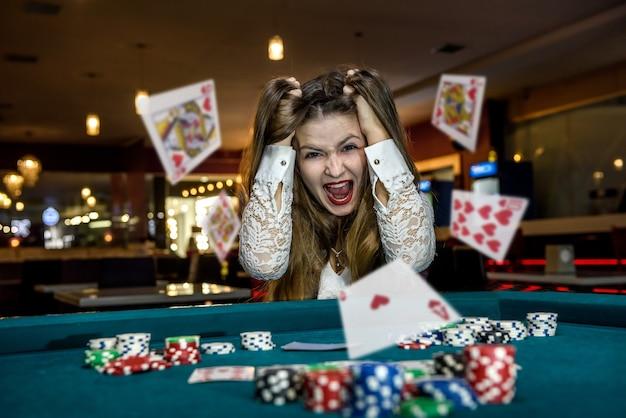 Femme bouleversée au casino avec des cartes qui tombent