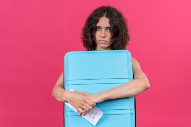 Une femme bouleversée aux cheveux courts portant un haut court vert tenant une valise bleue et des billets d'avion