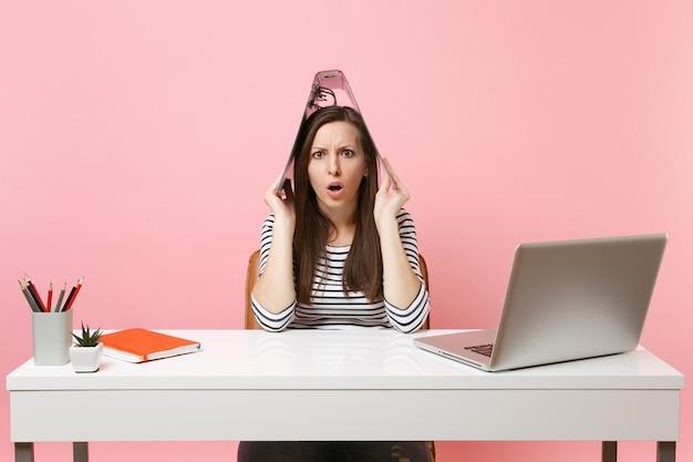 Femme bouleversée choquée tenant un dossier rouge avec un document papier au-dessus de la tête comme un toit travaillant sur un projet tout en étant assise au bureau avec un ordinateur portable isolé sur fond rose. carrière commerciale de réussite. espace de copie.
