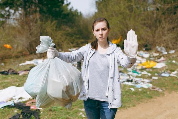 Femme bouleversée dans des vêtements décontractés nettoyant tenant des sacs poubelles et montrant un geste d'arrêt avec une paume dans un parc jonché