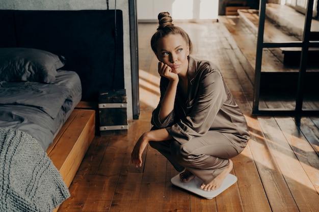Femme bouleversée et démotivée sur une balance électronique dans la chambre se demandant pourquoi ne peut pas perdre du poids malgré son nouveau régime, regardant de côté avec une expression de visage triste. perte de poids et mode de vie sain