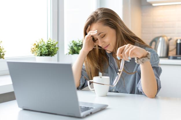 Femme bouleversée devant le moniteur d'ordinateur portable à l'intérieur de la maison.