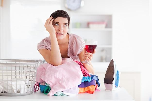 Femme bouleversée avec du vin et un tas de vêtements