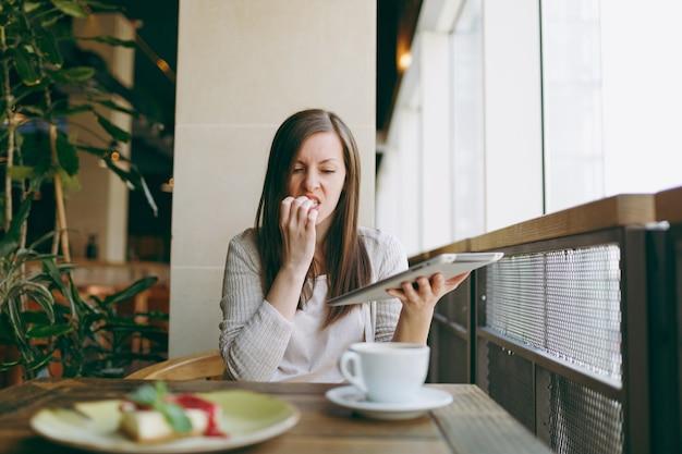 Une femme bouleversée est assise seule près d'une grande fenêtre dans un café avec une tasse de gâteau au cappuccino, se relaxant pendant le temps libre. une femme travaille, lit de mauvaises nouvelles sur une tablette pc, ronge des ongles dans un café. concept de mode de vie
