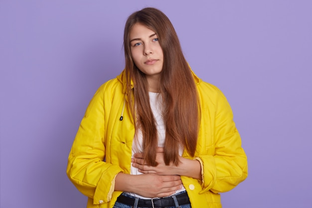 Femme bouleversée avec une expression triste, gardant les mains sur le ventre, ayant des douleurs, souffrant de maux d'estomac, posant isolée sur un mur violet.