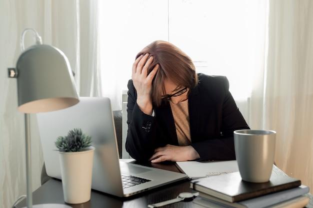 Femme bouleversée a fermé votre visage de mains près de son lieu de travail avec un ordinateur portable et une application de reprise.