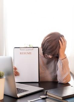 Une femme bouleversée a fermé votre visage de mains près de son lieu de travail avec un ordinateur portable et une application de reprise.