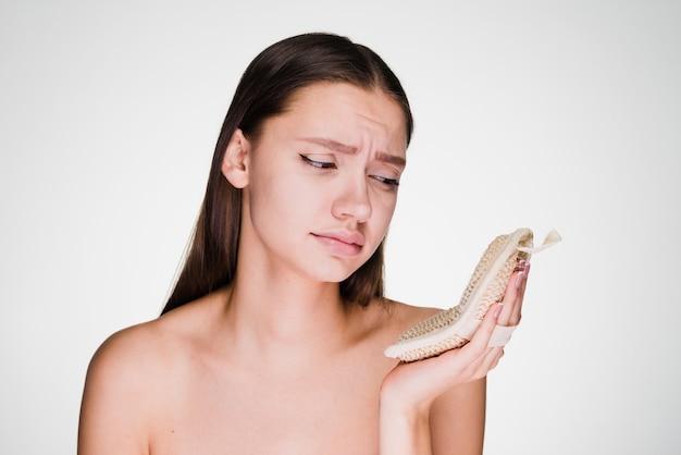 Femme bouleversée sur fond gris regardant l'éponge
