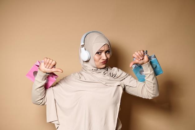 Femme bouleversée en hijab et écouteurs tenant des sacs en papier cadeau rose et bleu dans les mains et montrant les pouces vers le bas, exprimant son insatisfaction