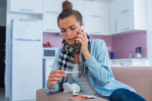 Femme bouleversée malade à la recherche sur un thermomètre médical et appelant le médecin de famille à la maison