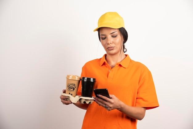 Femme bouleversée avec des tasses à la recherche de téléphone
