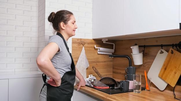 Une femme bouleversée vient dans la cuisine et voit de la vaisselle sale dans l'évier
