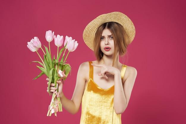 Femme avec un bouquet d'expression mécontent fleurs fond rose