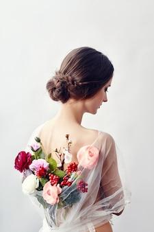 Femme avec un bouquet de fleurs artificielles derrière elle