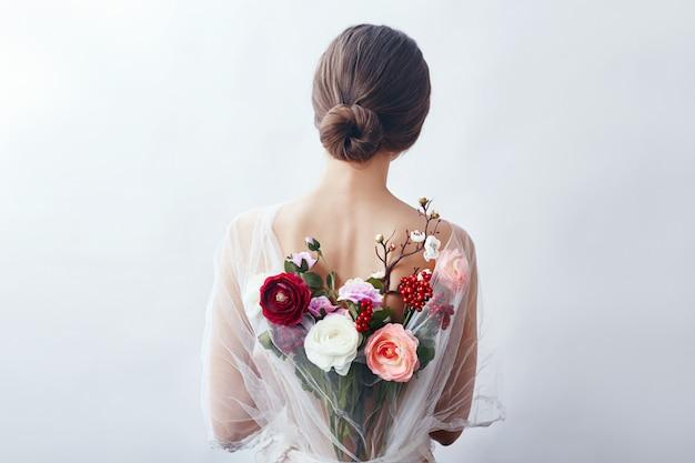Femme avec un bouquet de fleurs artificielles derrière